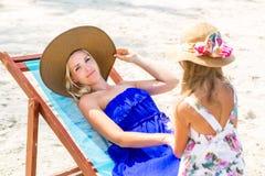 Nettes Mädchen und schöne Mutter auf dem Strand Stockfoto