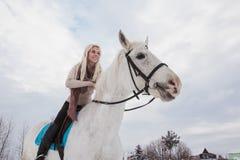 Nettes Mädchen und Schimmel im Freien in einem Winter Lizenzfreies Stockfoto