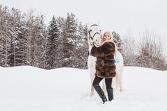 Nettes Mädchen und Schimmel im Freien in einem Winter Stockbilder