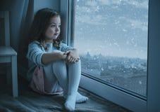 Nettes Mädchen, welches das Stadtbild beim Schneien betrachtet stockfotografie