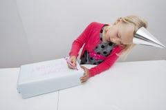 Nettes Mädchenschreiben auf Geburtstagsgeschenk bei Tisch im Haus Lizenzfreies Stockfoto