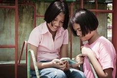Nettes Mädchenspieltelefon am Spielplatz stockfotografie