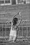 Nettes Mädchentanzen unter Wasserstrahlen im Stadtbrunnen Stockfoto