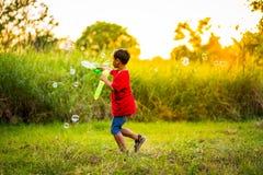 Nettes männliches Kind fängt Seifenblasen in der Natur Lizenzfreies Stockbild
