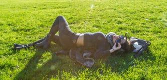 Nettes Mädchen, das auf grünem Gras liegt und unter der Sonne sich entspannt Stockfotografie