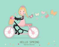 Nettes Mädchen, das ein bicyle mit Frühlingsblume und -schmetterlingen reitet Stockfotos