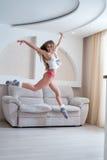 Nettes Mädchen, das während des Sprunges im Wohnzimmer aufwirft Stockfotos