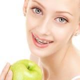 Nettes Mädchen in den Klammern mit Apfel auf weißem Hintergrund Lizenzfreie Stockfotografie