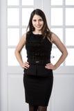 Nettes Mode-Modell-Schwarzkleid, das hinten in den Studiodachbodenausgangsinnentüren aufwirft und lächelt Stockfotografie