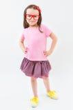 Nettes Modehändlermädchen in den rosa des Kleidert-shirt und -rockes roten Glasrahmen Stockfotos