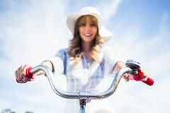 Nettes modisches blondes Reiten ihr Fahrrad Lizenzfreie Stockfotos