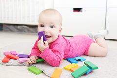 Nettes 6-monatiges Baby spielt hölzernes mehrfarbiges meccano zu Hause Lizenzfreies Stockfoto