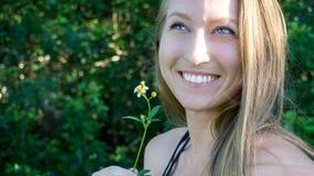 Nettes nahes Porträt eines jungen Blondinegesichtes, das mit blauen klaren Augen lächeln und der Gänseblümchenblume lokalisierte  lizenzfreies stockfoto