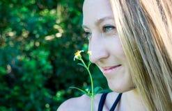 Nettes nahes Profilporträt des jungen blonden Frauengesichtes, das mit blauen klaren Augen lächelt und eine Gänseblümchenblume lo lizenzfreie stockfotos