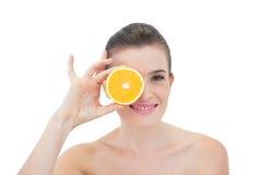 Nettes natürliches braunes behaartes Modell, das ihr Auge mit einer orange Hälfte versteckt Lizenzfreie Stockfotografie