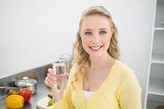 Nettes nettes blondes haltenes Glas Wasser Lizenzfreie Stockbilder