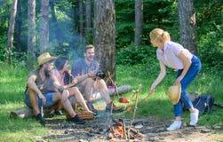 Nettes neues Lebensmittel und Korb auf dem Gras Touristenwanderer sitzen auf Klotzentspannungswartepicknicksnack Firma, die Wande lizenzfreie stockfotografie