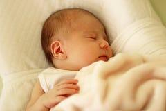 Nettes neugeborenes Baby, das auf einem wei?en Bett unter beige Decke schl?ft stockfoto
