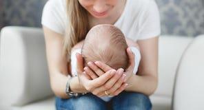 Nettes neugeborenes Baby, das in den Armen der Mutter schläft Stockbilder