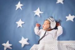 Nettes neugeborenes Baby, das im Bett liegt Kind des zweimonatigen Babys im Eulenhut schlafend auf blauer Decke lizenzfreie stockfotografie