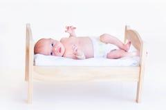 Nettes neugeborenes Baby in einer Windel, die in ein Spielzeugbett legt Lizenzfreies Stockfoto