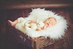 Nettes neugeborenes Baby im Bären, den Hut im Korb mit Spielzeugteddybären schläft, ist stockfotografie