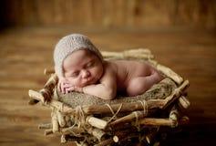 Nettes neugeborenes Baby mit einer wenigen Leinenkappe auf ihrem Kopf schläft in einem Korb stockfotografie