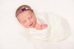 Nettes neugeborenes im Stirnband mit dem Blumenlächeln schlafend Lizenzfreies Stockfoto