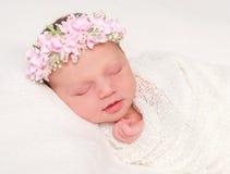 Nettes neugeborenes im Stirnband mit dem Blumenlächeln schlafend Lizenzfreies Stockbild