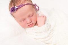 Nettes neugeborenes im Stirnband mit dem Blumenlächeln schlafend Stockfoto
