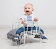 Nettes neugieriges Baby, das auf einem kleinen Bett sitzt Lizenzfreie Stockfotografie