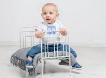 Nettes neugieriges Baby, das auf einem kleinen Bett sitzt Stockfotos