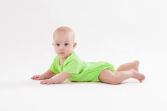 Nettes neugieriges Baby liegt auf ihrem Magen und dem Betrachten der Kamera Stockfotografie