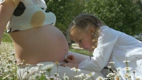 Nettes neugieriges kleines Mädchen, das auf den Bauch ihrer Mutter hört stock video