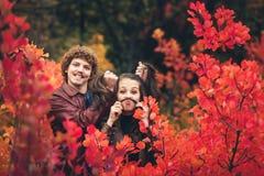 Nettes Paar ist frech und zeigt Gefühle zwischen roten Herbstbäumen lizenzfreies stockbild
