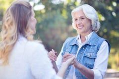 Nettes Pensionärhändchenhalten mit Enkelin im Park Lizenzfreies Stockfoto