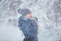 Nettes Porträt der jungen Frau, das mit Schnee im warmen woolen Hut und im Mantel im Winterpark spielt stockfoto