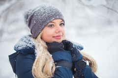 Nettes Porträt der jungen Frau, das mit Schnee im warmen woolen Hut und im Mantel im Winterpark spielt stockbilder