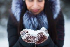 Nettes Porträt der jungen Frau, das Schnee in ihren Händen tragen warme Handschuhe hält lizenzfreie stockfotos