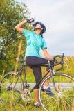 Nettes Porträt des jungen weiblichen Radfahrerathleten, der ein Wasser bre hat Lizenzfreies Stockfoto