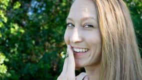 Nettes Porträt Gänseblümchen-Blumenunkrauts des jungen Blondinegesichtes des rauchenden, das mit den blauen klaren Augen lokalisi lizenzfreies stockfoto