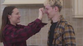 Nettes positives Mädchen befleckt Mehl auf dem Gesicht des Freundes in der Küche Glückliche junge Paare, die herum beim Kochen tä stock footage