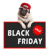 Nettes Pughündchen, das rote Kappe trägt und mit den Tatzen auf Zeichen mit Textschwarzem Freitag, auf weißem Hintergrund hängt lizenzfreie stockfotografie