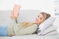 Nettes recht blondes Lesebuch, das auf angenehmem Sofa liegt Lizenzfreies Stockfoto