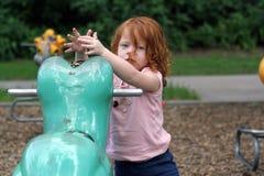 Nettes Redhead-Mädchen auf einem Spielplatz   Stockfoto
