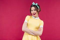 Nettes reizendes Pinupmädchen in der gelben Kleiderstellung und -c$lächeln stockfotografie