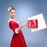 Nettes Retro Mädchen, das Einkaufstaschen anhält Stockfotografie