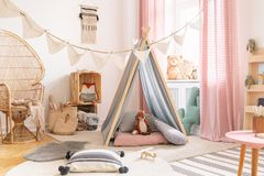 Nettes rosa kleines Prinzessinspielzimmer im skandinavischen Entwurf mit Pfaustuhl, -kissen, -teppichen, -spielwaren und -zelt mi lizenzfreie stockfotos