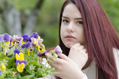 Nettes rotes Haar, das auf einem hölzernen Gartentisch sitzt stockfotografie