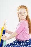 Nettes rothaariges Caucasain-Mädchen, das enorme Bleistifte hält Lizenzfreie Stockbilder
